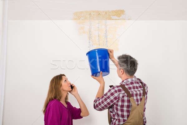 Worker Collecting Water In Bucket From Ceiling Stock photo © AndreyPopov