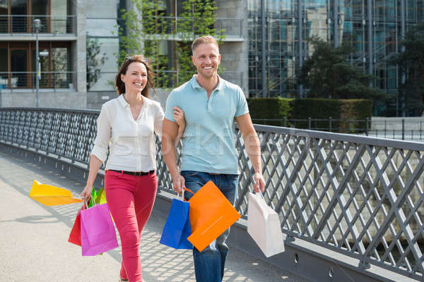 Couple Walking On Bridge With Shopping Bags Stock photo © AndreyPopov