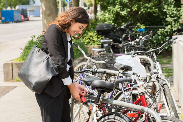 Young Businesswoman Locking Up Her Bicycle Stock photo © AndreyPopov