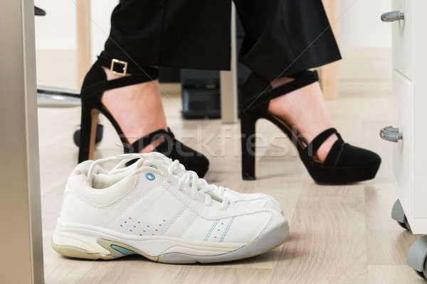 Sport Shoes Besides Businesswoman's Foot Stock photo © AndreyPopov