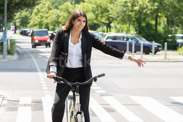 Young Businesswoman Showing Turn On Bicycle Stock photo © AndreyPopov