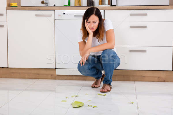 Unhappy Woman Looking At The Broken Plate On Floor Stock photo © AndreyPopov