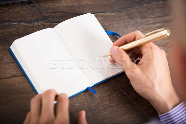 Businessperson Writing On Personal Diary Stock photo © AndreyPopov