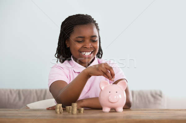 Girl Inserting Coins In Piggy Bank Stock photo © AndreyPopov