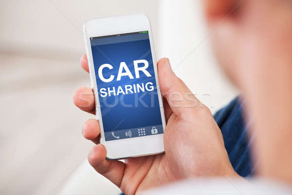 Hand Holding Smart Phone With Car Sharing App On Screen Stock photo © AndreyPopov