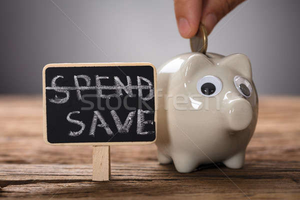 Hand Putting Coin In Piggybank By Spend Save Sign Stock photo © AndreyPopov