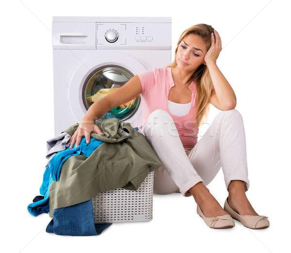 Aggódó fiatal nő halom szennyeskosár ül mosógép Stock fotó © AndreyPopov