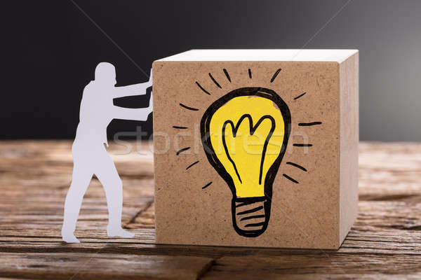 Paper Man Pushing Wooden Block With Lightbulb Symbol Stock photo © AndreyPopov
