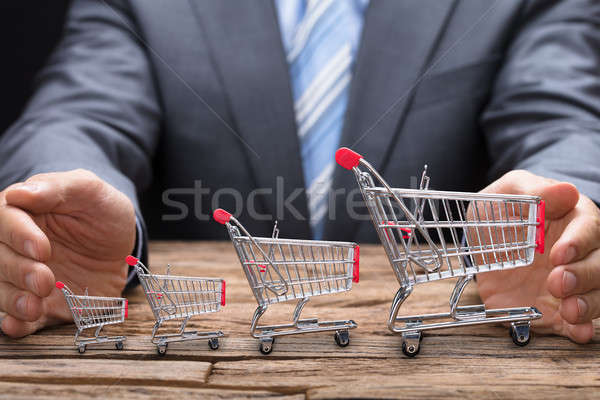 Businessman Covering Various Shopping Carts On Table Stock photo © AndreyPopov
