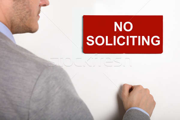 Businessman Knocking Door With No Soliciting Nameplate Stock photo © AndreyPopov