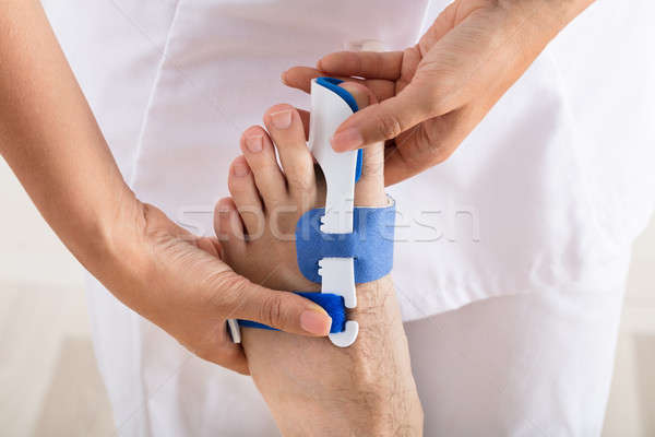 Orthopedist Fixing Plaster On Injured Man's Foot Stock photo © AndreyPopov