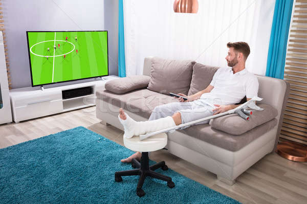 Man With Broken Leg Watching Football Match On Television Stock photo © AndreyPopov