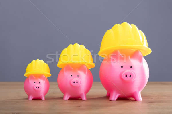 Increasing Pink Piggy Banks With Yellow Hard Hat Stock photo © AndreyPopov