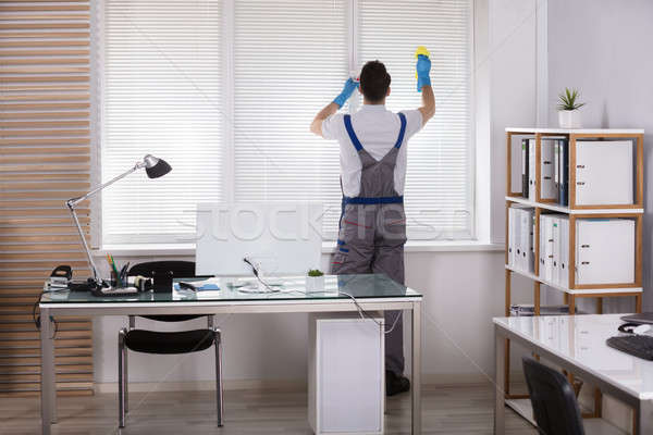 Male Worker Cleaning Window Blinds With Sponge Stock photo © AndreyPopov