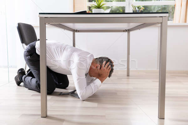 Afraid Businessman Hiding Under Table Stock photo © AndreyPopov