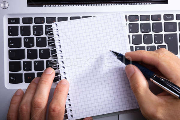 Person's Hand Writing On Spiral Notepad Stock photo © AndreyPopov