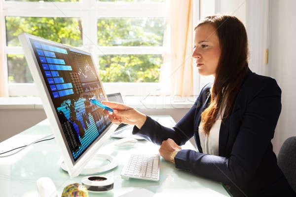 Businesswoman Analyzing Graphs On Computer Stock photo © AndreyPopov