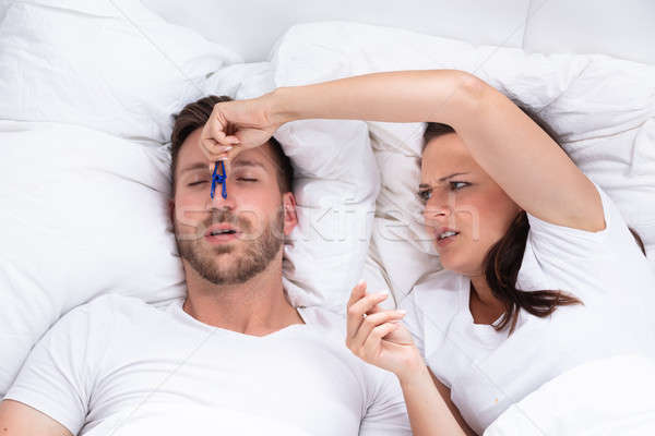 Woman Trying To Stop Man's Snoring With Clothespin Stock photo © AndreyPopov