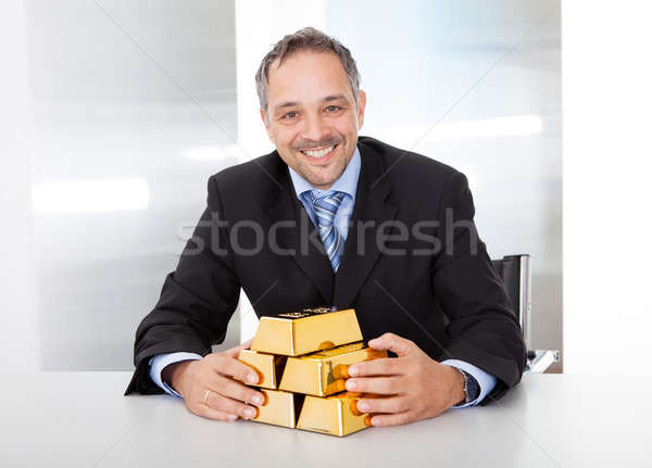 Businessman with golden bars Stock photo © AndreyPopov