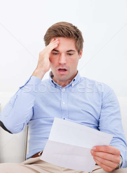Young man shocked reading letter Stock photo © AndreyPopov