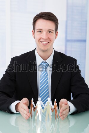 Businessman Protecting Team Of Paper People At Desk Stock photo © AndreyPopov