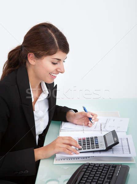 Businesswoman Calculating Bills At Desk Stock photo © AndreyPopov