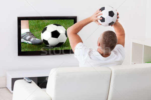 Soccer fan watching a game on television holding a soccer ball Stock photo © AndreyPopov