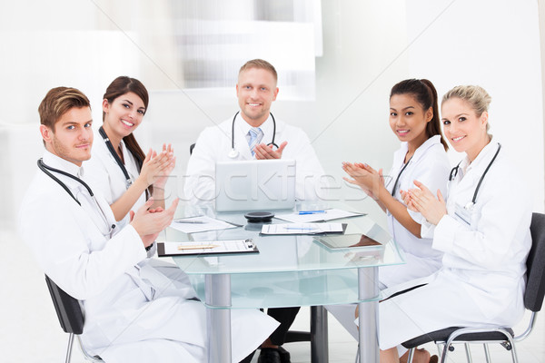 Confident Doctors Applauding At Desk Stock photo © AndreyPopov