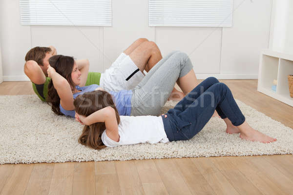 Family Doing Situps On Rug At Home Stock photo © AndreyPopov