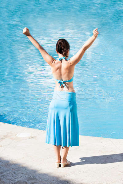 Rear view of woman with arms raised standing at poolside Stock photo © AndreyPopov