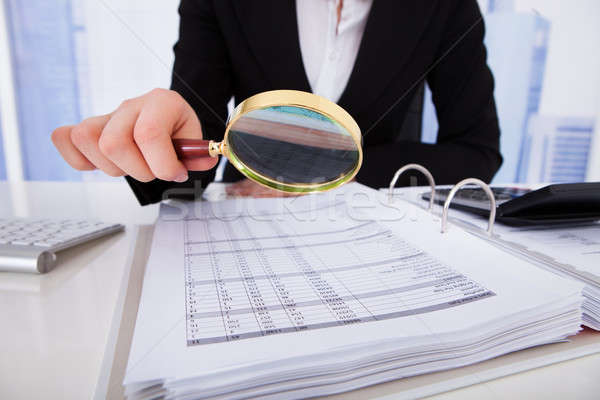 Businesswoman Scrutinizing Bills With Magnifying Glass Stock photo © AndreyPopov