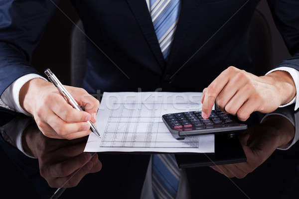 Businessman Calculating Financial Expenses At Desk Stock photo © AndreyPopov