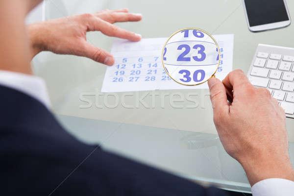 ストックフォト: ビジネスマン · 見える · カレンダー · 虫眼鏡 · 画像 · デスク