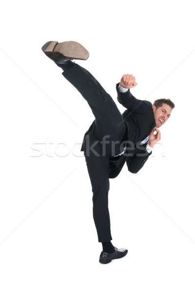 Businessman Kicking Over White Background Stock photo © AndreyPopov