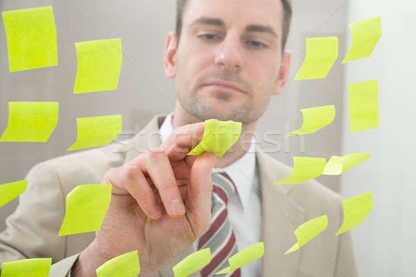 üzletember néz tapadó jegyzetek üveg fal Stock fotó © AndreyPopov