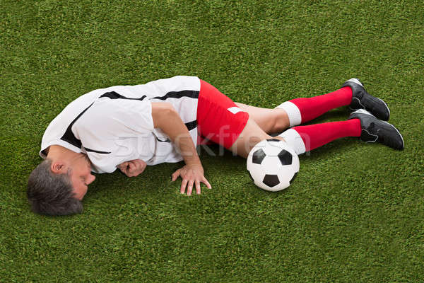 Injured Soccer Player Lying On Grass Stock photo © AndreyPopov