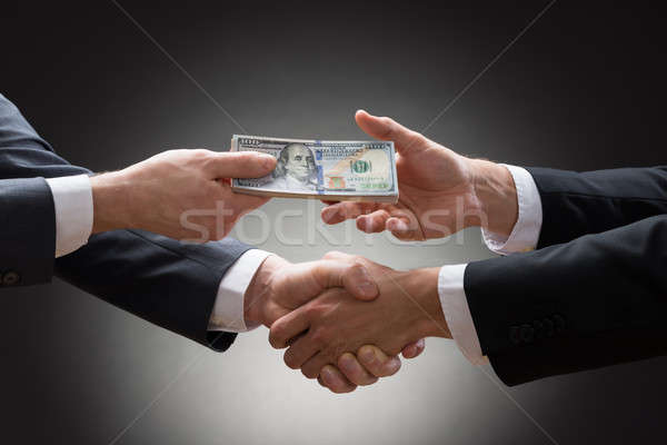 Businessmen Shaking Hands And Receiving Money Stock photo © AndreyPopov