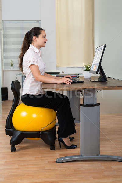 Businesswoman Sitting On Fitness Ball With Computer At Desk Stock photo © AndreyPopov