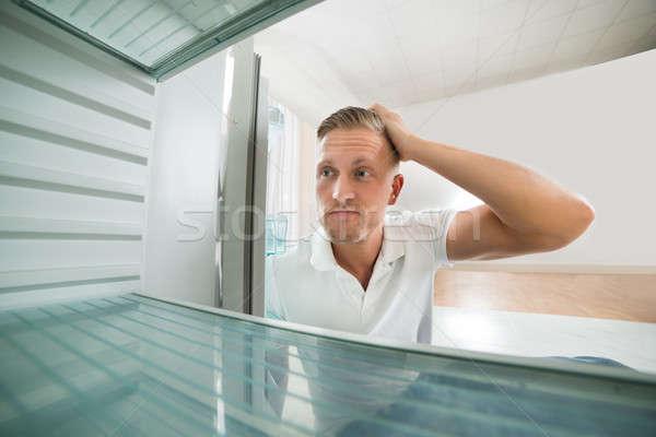 Man Looking In Empty Refrigerator Stock photo © AndreyPopov