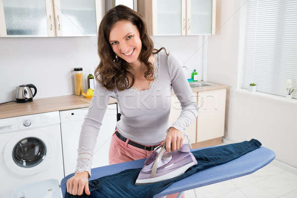 Happy Woman Ironing Trousers Stock photo © AndreyPopov