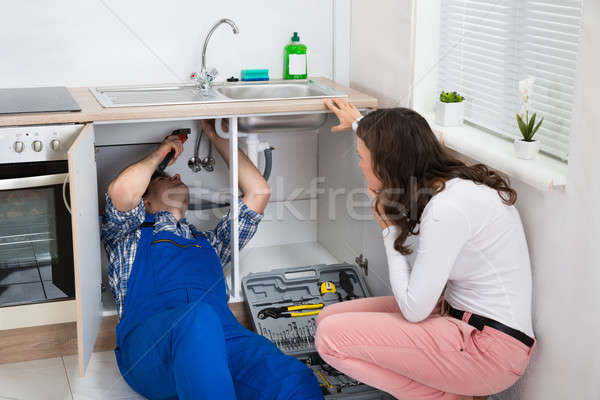 Repairman Repairing Pipe While Woman In The Kitchen Stock photo © AndreyPopov