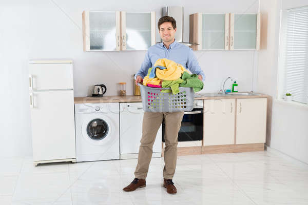 Man Carrying Basket With Heap Of Clothes Stock photo © AndreyPopov