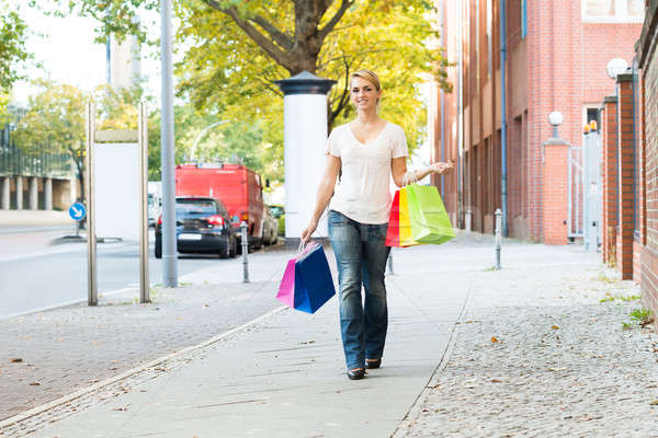 Happy Woman Carrying Shopping Bags On Sidewalk Stock photo © AndreyPopov