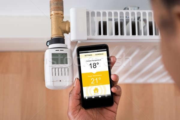 Temperatura termostato telefono cellulare primo piano persone mano Foto d'archivio © AndreyPopov