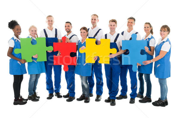 Confident Janitors Holding Jigsaw Pieces In Row Stock photo © AndreyPopov