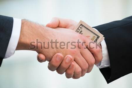 Businessman Bribing Partner While Shaking Hand Stock photo © AndreyPopov