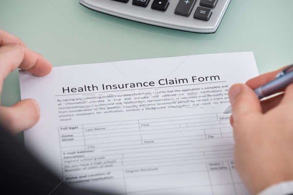 Person Filling Health Insurance Claim Form Stock photo © AndreyPopov
