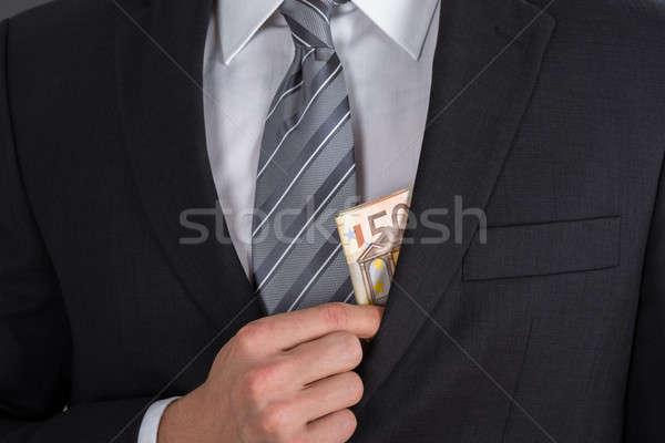 Businessman Putting Bribe Money In Suit Pocket Stock photo © AndreyPopov
