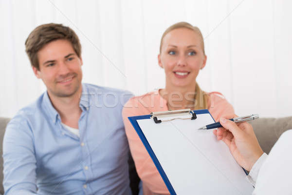 Stock photo: Consultant With Clipboard In Front Of Smiling Couple