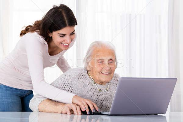Dos sonriendo mujeres usando la computadora portátil ayudar Foto stock © AndreyPopov